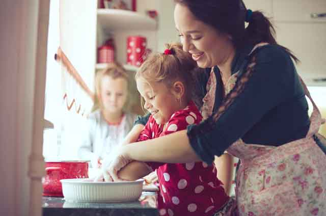 Adult cooking with children with hands in a bowl in a bowl