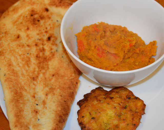 bowl of dhal with nan bread and bhaji on the side