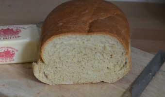 half-loaf-white-bread-on-bread-board-with-knife-and-block-of-butter