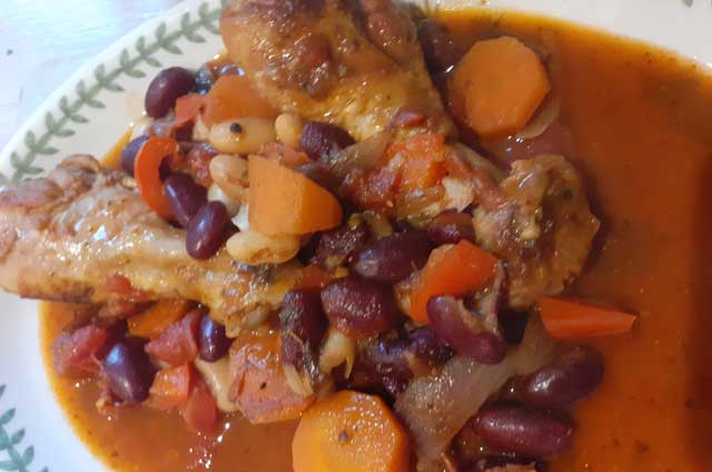 Chicken thighs and chicken drumsticks cooking in a casserole with vegetables
