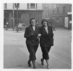 two 1920s ladies walking down the street arm in arm