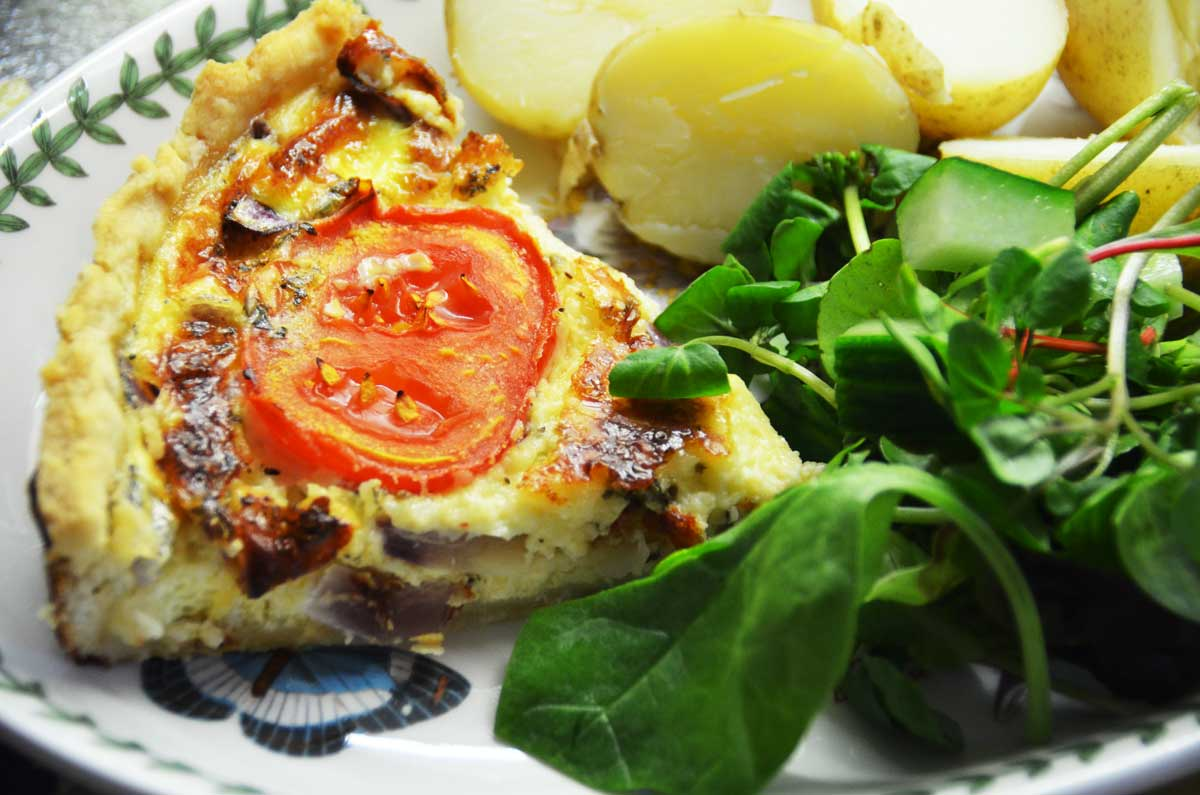 slice of cheese and tomato quiche served with new potatoes and green salad leaves