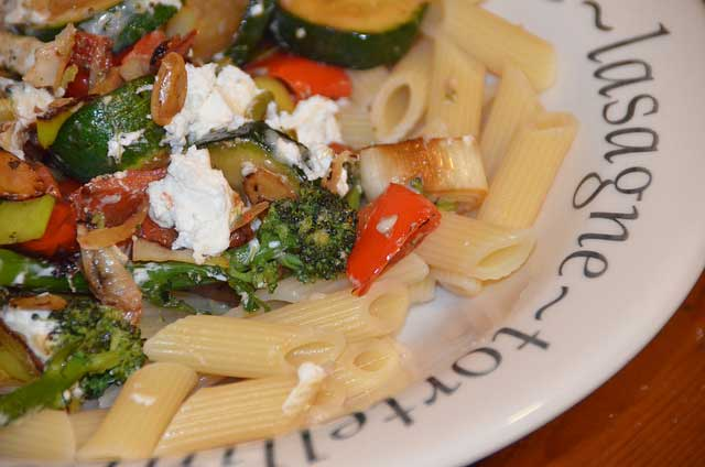 Goats cheese, peppers and a variety of vegetables on a bed of penne pasta