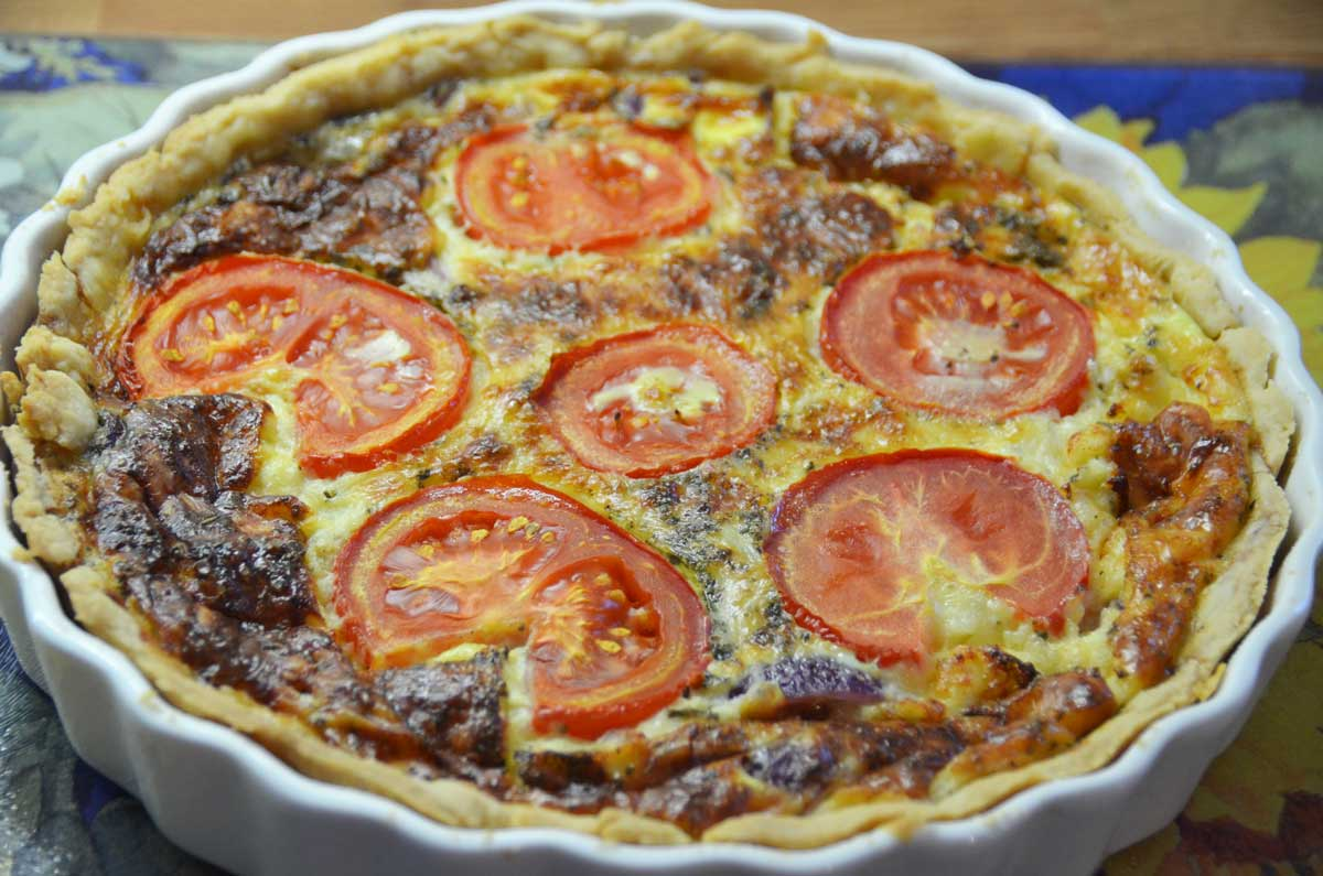 whole quiche in flan with sliced tomatoes on top
