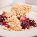 portion of apple and blackberry crumble showing fruit and crumble