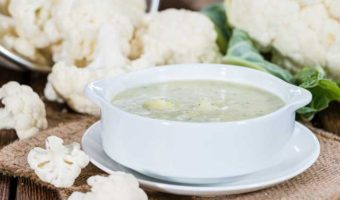 bowl of cream coloured soup with cauliflower florets next to it