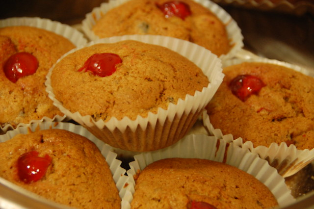 6 small brown christmas muffins with cherry in the middle