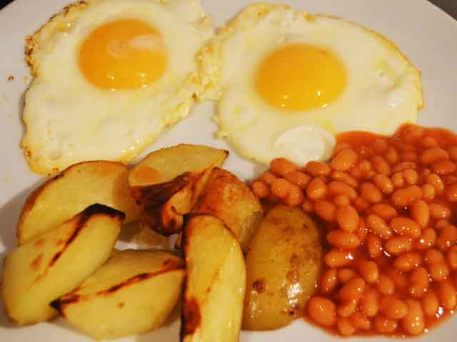 two fried eggs with potato wedges and beans on a plate