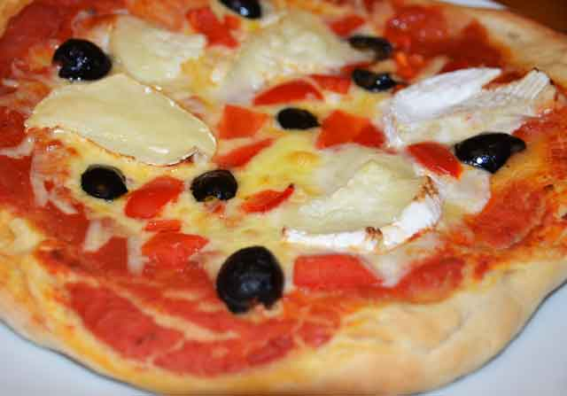 whole pizza with goats cheese and olives topping