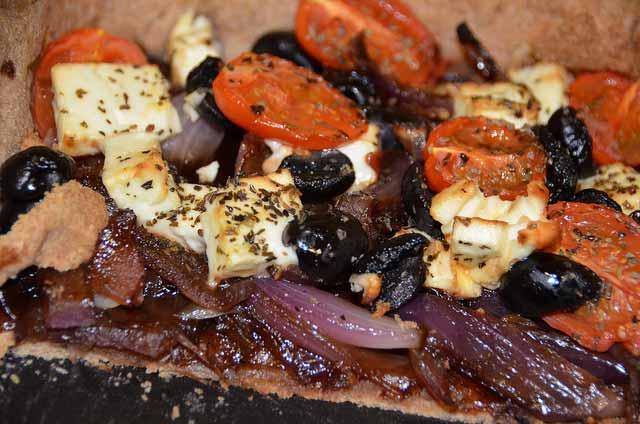 Easy to make Tart of red onions, feta cheese, olives and tomatoes on a pastry base