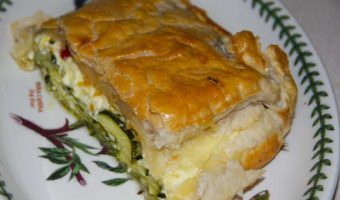 portion of pie in puff pastry showing courgette slices inside