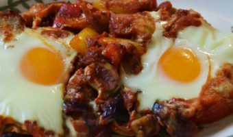 serving of two eggs in tomato and pepper sauce on a plate