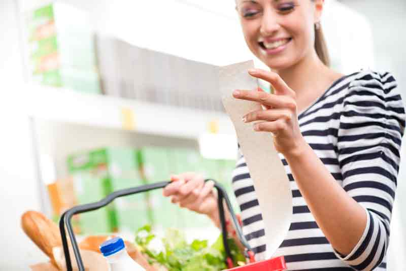 woman with shopping basket looking at till receipt and smiling