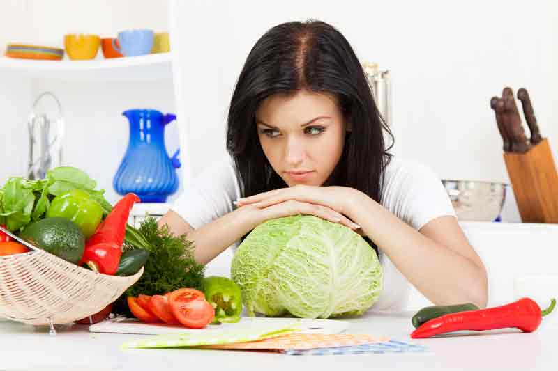 woman with cabbage looking quizzical