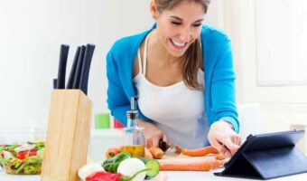 woman looking at tablet whilst cooking in kitchen