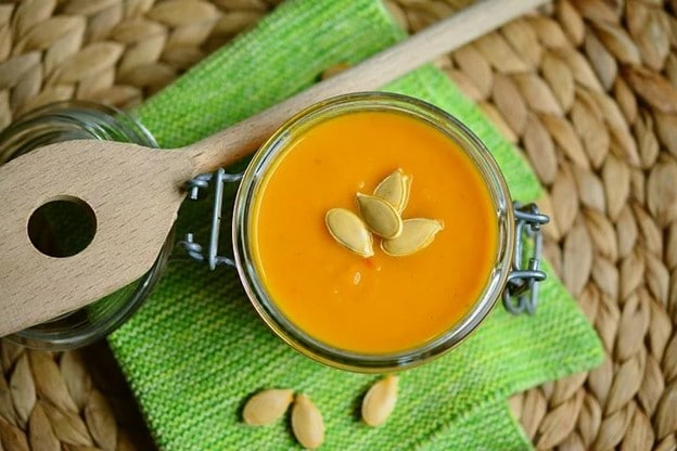 pumpkin soup with wooden spoon on table